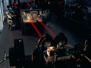 The PRIMA instrument for the VLT Interferometer is shown here during testing in Garching. The two combined beams of the PRIMA fringe sensor unit (FSU) B are seen, in red metrology laserlight, joining the FSU's beam combiner in the background to the fibre injection optics. When complete the facility is expected to provide improvements in VLTI sensitivity, along with astrometry to better than 100 microarcseconds.